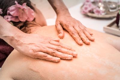 Hand scrubbing salt on woman back for Skincare